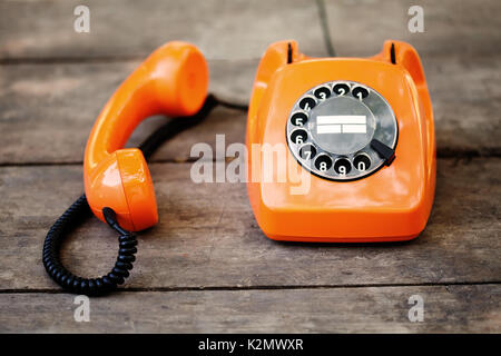 Busy retro phone orange color, handset receiver on wooden textured background. Shallow depth field photography - Stock Photo