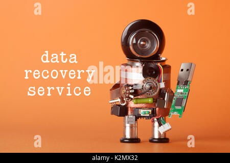 Data recovery service concept. Robotic character with usb flash stick. fun toy black helmet head green storage chip - Stock Photo