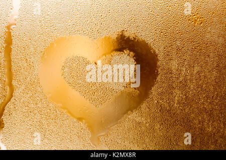 Love heart shape and raindrops textured pattern. Abstract golden color window with water droplet, liquid bubbles. - Stock Photo