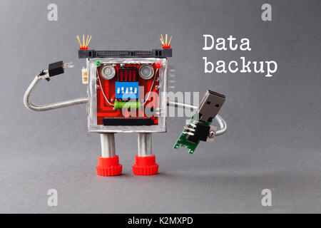 Data backup concept. Robotic character with portable usb device flash stick. Macro view, gray background - Stock Photo