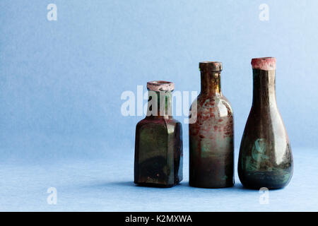 Vintage ink bottles on blue paper background. Aged dirty glass accessories. copy space, horizontal photo - Stock Photo