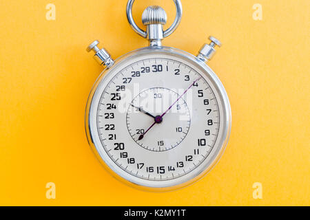 Retro style stopwatch chronometer on yellow paper textured background. Sport competition time management concept. - Stock Photo