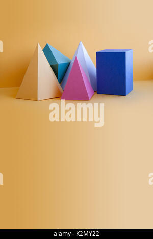 Colorful solid figures still life background. Three-dimensional prism pyramid rectangular cube objects on orange. - Stock Photo