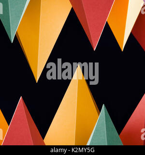 Colorful abstract geometric shapes on black background. Three-dimensional pyramid triangular. Yellow blue pink malachite - Stock Photo