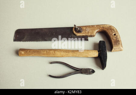 Handyman instrument hand saw hammer pliers. Vintage carpentry service work equipment on textured paper background. - Stock Photo