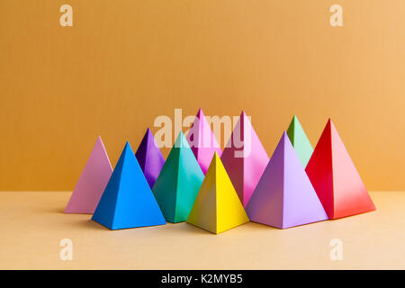 Colorful abstract geometric figures still life. Three-dimensional pyramid prism rectangular cube on orange background. - Stock Photo
