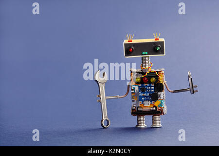 Robot serviceman with hand wrench and screwdriver on blue background. Abstract mechanical toy worker made of electronic - Stock Photo