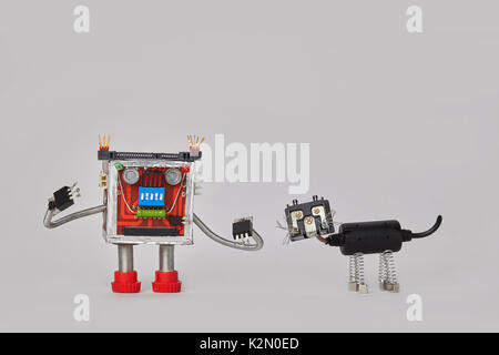 Colorful robot and machanical black cat character. Funny electric components toys on gray background. Copy space. - Stock Photo