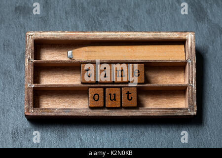 Time out concept. Vintage box, wooden cubes with old style letters, retro style pencil. Gray stone textured background. - Stock Photo