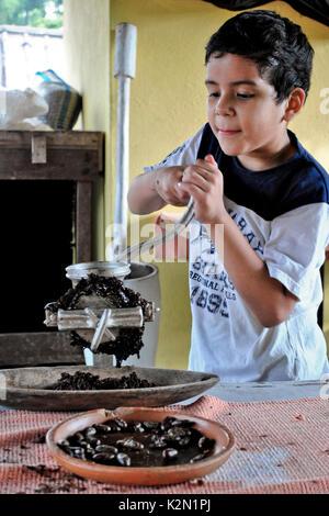 A kid grinding cocoa beans (Theobroma cacao).  Guayas.  Ecuador.