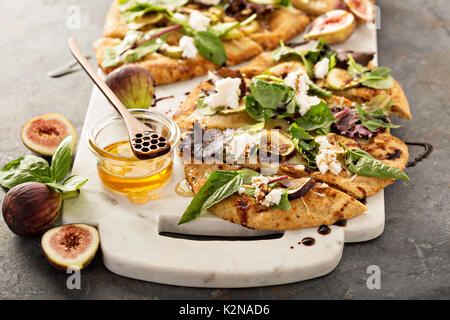 Flatbread fall pizza with balsamic, figs, cheese and salad leaves - Stock Photo
