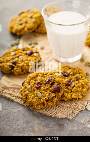 Breakfast oatmeal cookies with pumpkin puree, cranberry and seeds with milk - Stock Photo