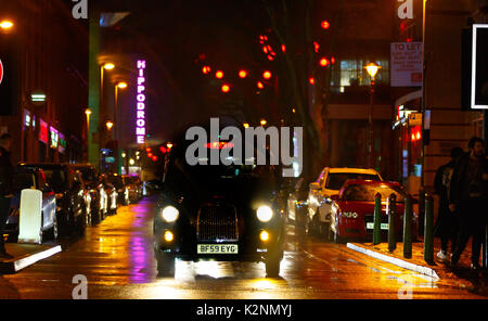 Bustling city centre street scene after rain with wet roads and reflections, many coloured lights and in Chinatown - Stock Photo
