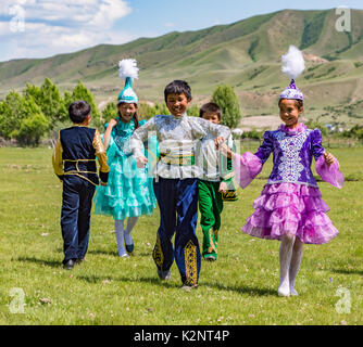 Children play a game in a field, wearing traditional costumes in Kazakhstan on June 3, 2017 - Stock Photo
