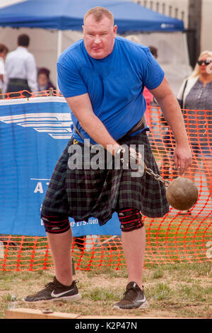 A hefty kilted contestant in the hammer throwing event swings his 16-pound ball at an ethnic Scottish festival in - Stock Photo