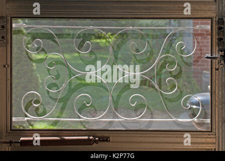 Mid-century decorative screen grate on a window in a door with grass and a patio behind it - Stock Photo
