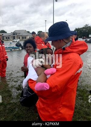Port Arthur, United States. 30th Aug, 2017. U.S. Coast Guard Petty Officer 3rd Class Ryan Hicks rescues a child - Stock Photo