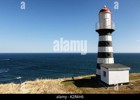Striped old building of Petropavlovsky Lighthouse (founded in 1850) - oldest lighthouse in Russian Far East, located - Stock Photo