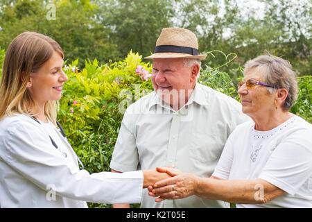 Young female medical doctor talking to elderly couple outdoor in the park - Stock Photo