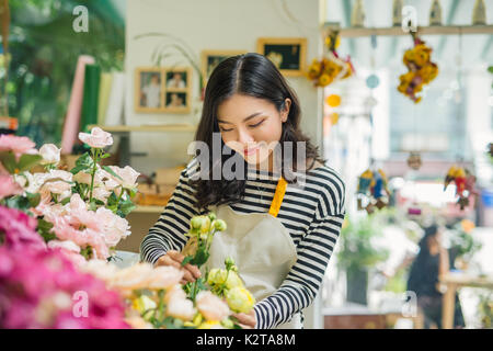 Portrait of young business woman florist working at flower shop - Stock Photo