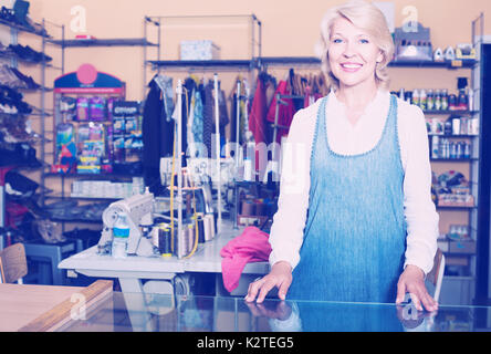Smiling mature woman tailor standing in sewing workshop - Stock Photo