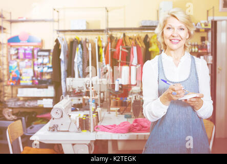 friendly smiling mature woman tailor standing in sewing studio ready to take order - Stock Photo