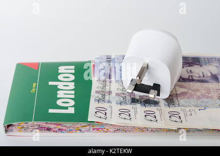 White travel power adapter, European to UK and map of London and British pounds. - Stock Photo