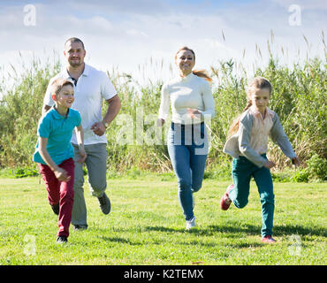 Cheerful young parents  with two kids playfully running on the green lawn. Selective focus - Stock Photo
