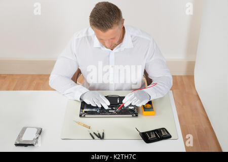 Young Man Examining Laptop Motherboard With Multimeter At Desk - Stock Photo