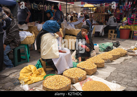 April 29, 2017 Otavalo, Ecuador: indigenous quechua women selling grains on the street in the Saturday market - Stock Photo
