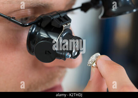 Close-up Of Jeweler Looking Ring Through Magnifying Loupe - Stock Photo