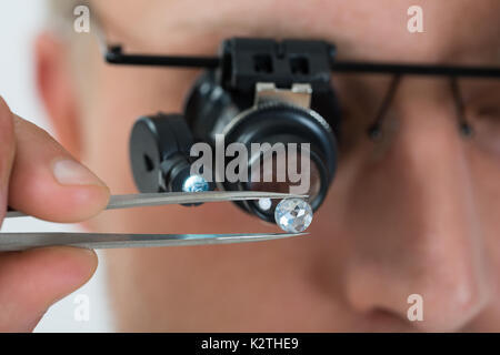 Close-up Of Person Looking At Diamond With Magnifying Loupe - Stock Photo