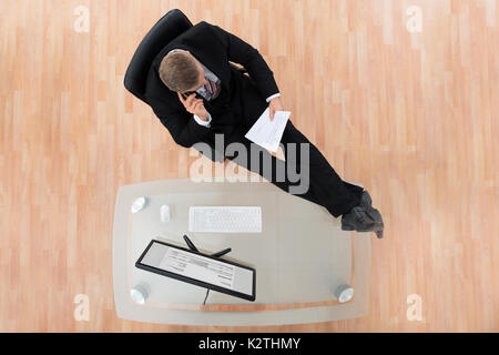 Businessman Reading Document While Sitting At The Desk In Office - Stock Photo
