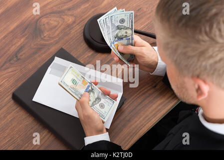 Close-up Of Judge Counting Money At Desk In Courtroom - Stock Photo
