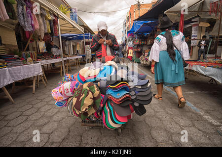 April 29, 2017 Otavalo, Ecuador: mobile vendor selling hats from a cart in the Saturday market - Stock Photo
