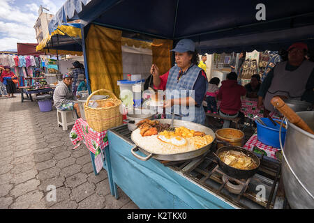 April 29, 2017 Otavalo, Ecuador: indigenous quechua women are preparing food on the street in the Saturday market - Stock Photo