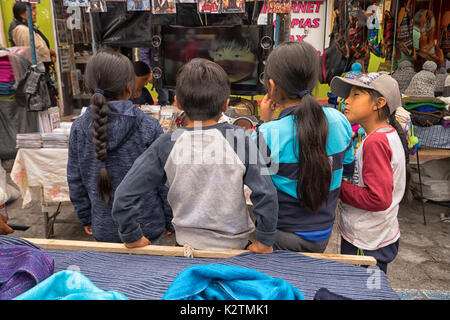 April 29, 2017 Otavalo, Ecuador: indigenous quechua children watching TV on the street in the Saturday market - Stock Photo