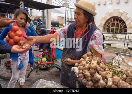 May 6, 2017 Otavalo, Ecuador: produce vendor in the Saturday market giving change to costumer - Stock Photo