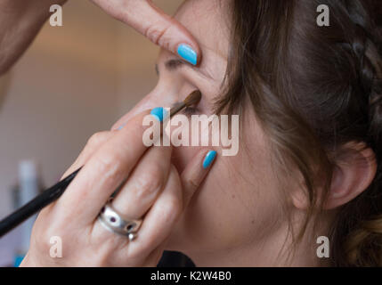 A young woman undergoing an eye shadow application from a professional make up artist with light blue painted fingernails. - Stock Photo