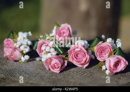 Flower arrangement for wedding centerpiece featuring small pink roses and baby's-breath, positioned on a tree stump, - Stock Photo