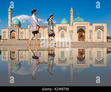 Two women stroll in front of the Khast-Imam mosque, in Tashkent, Uzbekistan, reflected in puddle of water on May - Stock Photo