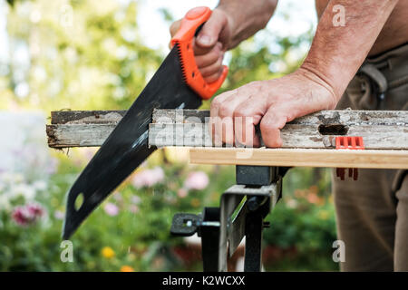 Caucasian man working cutting plank with handsaw outdoor in summer. - Stock Photo