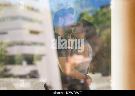 Portrait of couple in love kissing passionately behind window - Stock Photo