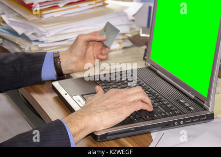 Business man shopping online, using laptop and credit card on green screen - Stock Photo