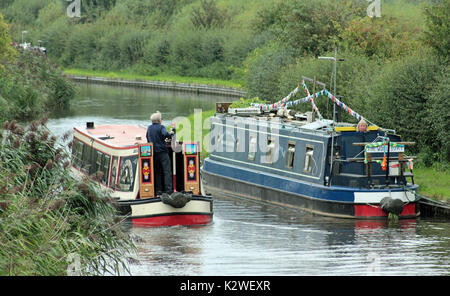 "The narrow boat ""Emma Maye"" is passed by another boat as she is moored along the towpath at Walton Bridge on the - Stock Photo"