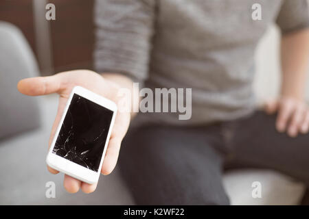 Man showing destroyed white smart phone - Stock Photo