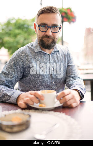 Bearded man sitting in cafe-garden and having cappuccino
