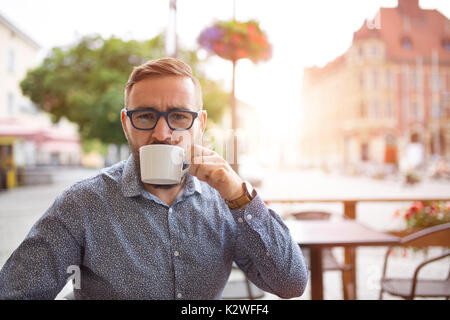 Elegant man drinking cappuccino in cafe-garden at old town