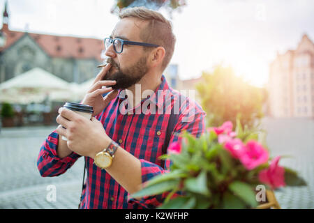 Man sitting in cafe garden and smoking cigarette in morning sunlight - Stock Photo