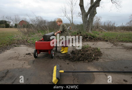 YOUNG BOY SHOVELING SOIL IN TO RED WAGON, TEXAS - Stock Photo